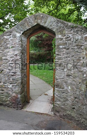 stone arch and door to garden with grass on other side - stock photo