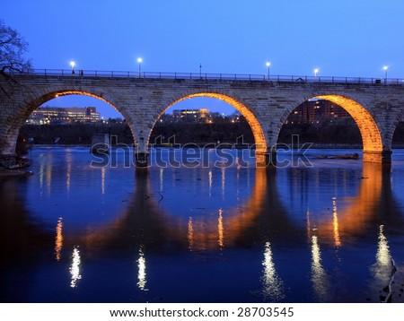 Stone Arch bridge in downtown Minneapolis at night - stock photo