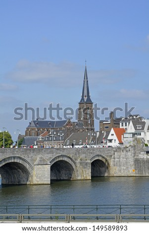 Stone arched Saint Servatius  bridge crossing the River Meuse in Maastricht with church spire beyond - stock photo