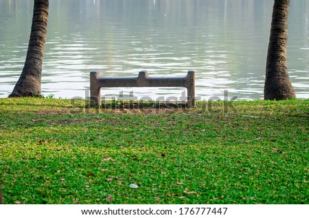 stone bench near the lake - stock photo