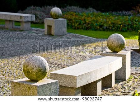 Stone bench with stone balls - stock photo