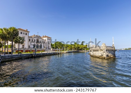 Stone breakwater barge and Magnificent Mansion Vizcaya on Biscayne bay under blue sky - stock photo