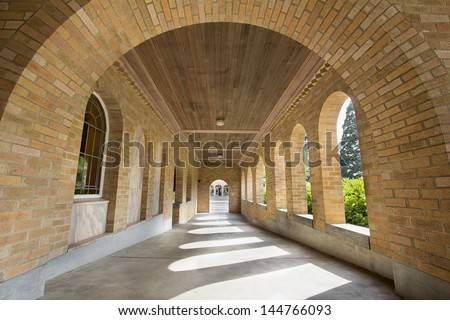 Stone Bricks Arch Walkway with Wood Planks Ceiling - stock photo
