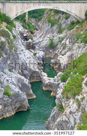 Stone bridge above narrow gorges and river in Saint Guilhem le Desert, Languedoc Roussillon, France - stock photo