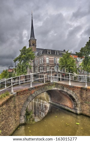 Stone bridge across an canal and a small church in the historical center of Delft, Holland - stock photo