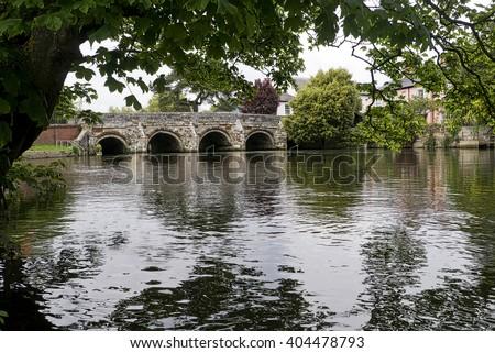 Stone bridge; ancient stone bridge over river in English countryside  - stock photo