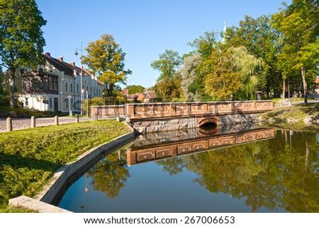 "Stone bridge, reflected in the pond, Kuldiga, Latvia. On the building an inscription on Lettish language ""Kuldiga's court"" - stock photo"