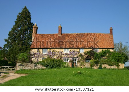 Stone built wisteria clad traditional cottage in rural Oxfordshire England - stock photo