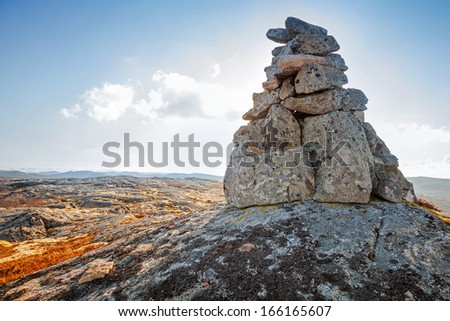 Stone cairn as a navigation mark on the top of Norwegian mountain - stock photo