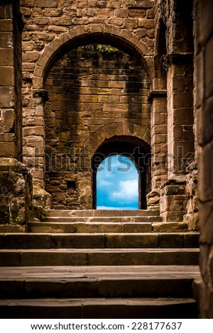 Stone castle steps and arched doors leading to blue sky - stock photo