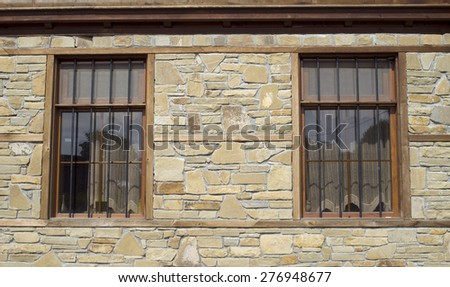 Stone cladding plates on the wall with two window