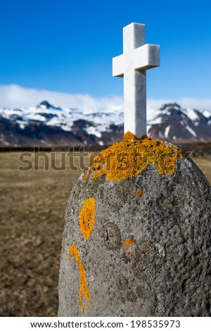 Stone cross and snow covered mountains in Budir, Iceland - stock photo