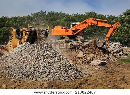 Stone crusher and crane in working - stock photo