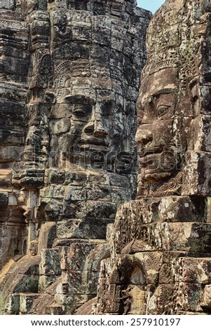 Stone faces of The Bayon, part of the temple complex of Angkor in western Cambodia - stock photo
