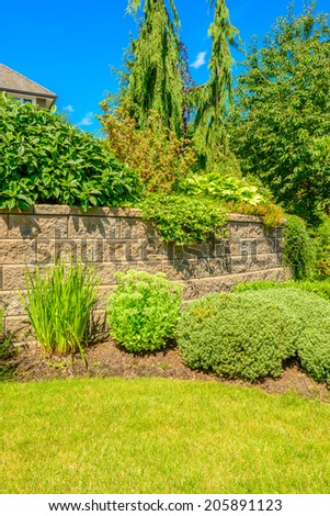 Stone fence with green lawn and landscape - stock photo