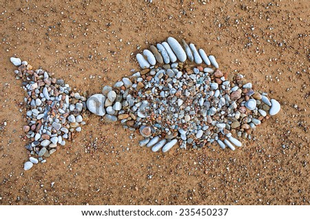 Stone fish symbol of pebbles on the sea boulder - stock photo