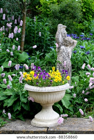 Stone Flower container with pansies and a stone statue - stock photo