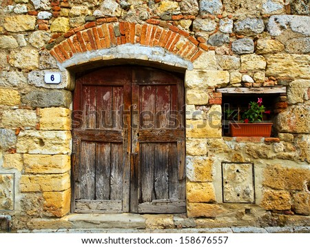 Stone house facade with old door and a small window - stock photo