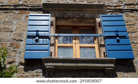 Stone House with Blue Window Shutters. Window with opened blue shutters on old stone house. - stock photo