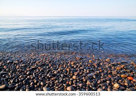 stone in the coastline sunrise and light ocean     white sky - stock photo