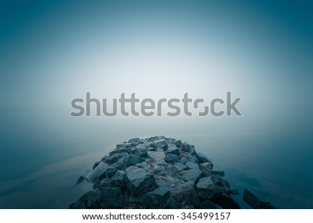 Stone jetty in the autumn foggy river. - stock photo