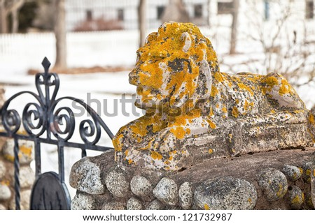 Stone lion covered in fungus flanking a iron garden gate. - stock photo