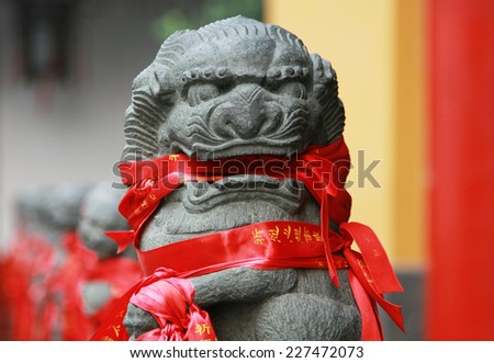 Stone lion figure with traditional prayer ribbons in buddhist temple - stock photo