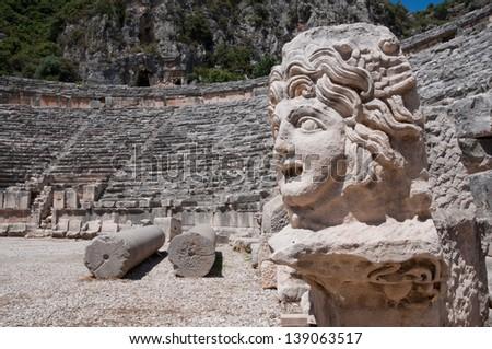 Stone mask and ancient amphitheater, Myra (Turkey ) - stock photo