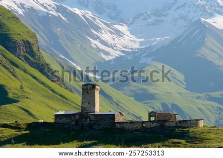Stone medieval church in a mountain valley. View of Mount Shhara. Ushguli community, Zemo Svaneti, Georgia - stock photo