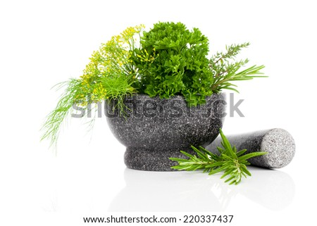 Stone mortar with green herbs, on white background - stock photo