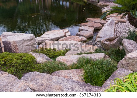 Stone path in a Japanese Garden across a tranquil pond. - stock photo