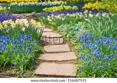 Stone path winding in spring flower garden - stock photo
