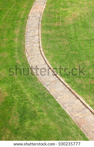 Stone path with grass growing around  ( top view on park) - stock photo
