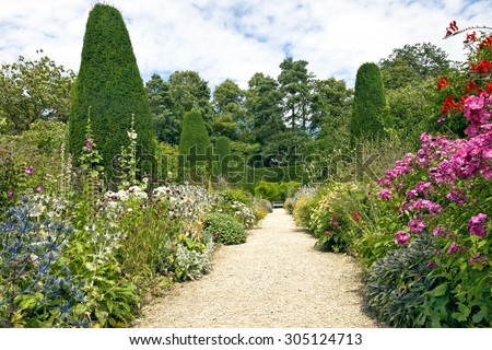 Stone pathway leading to a white bench, with cottage colourful flowers in bloom on both sides, shaped conifers, shrubs and tall trees in an English garden on a sunny summer day - stock photo