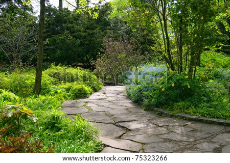 Stone pathway passing through a garden - stock photo