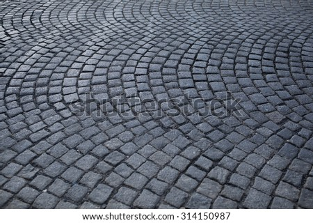 Stone pavement texture. Granite cobblestoned pavement background. Abstract background of old cobblestone pavement with shallow depth of field - stock photo