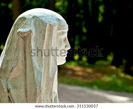 Stone profile of a beautiful young woman in the park in summer - stock photo