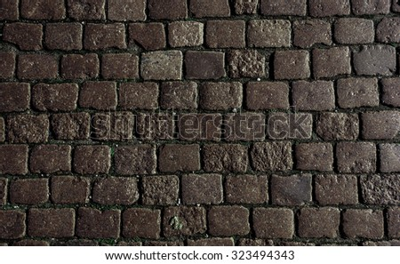 Stone road texture.  stone block paving. Stone blocks in the walkway. Stone pavement texture. Granite cobble stoned pavement background. Abstract background of old cobblestone pavement close-up. - stock photo
