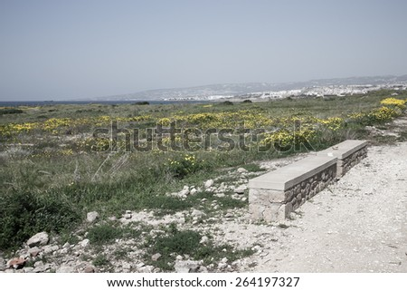Stone seat on mountain above the sea on a background of the sky and city - stock photo