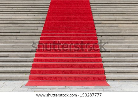 Stone staircase with red carpet - stock photo
