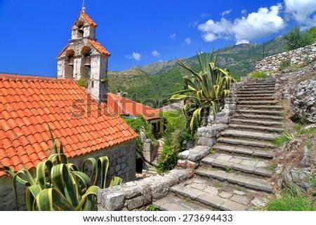 Stone stairs ascending around traditional stone church in Montenegro - stock photo