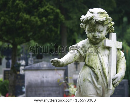 Stone statue of a child holding a cross. - stock photo