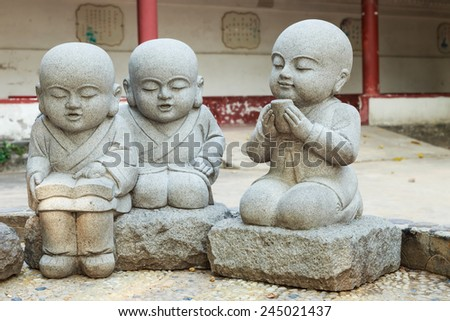 Stone statue of learning and relax Chinese monks in temple - stock photo