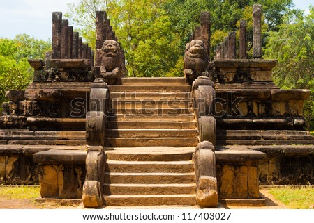 Stone steps and lion carvings lead to the front of the ancient audience hall, part of the ruins of the former capitol in Polonnaruwa, Sri Lanka - stock photo
