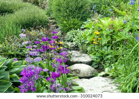 Stone steps going through charming English cottage garden full of colourful flowers and shrubs - stock photo