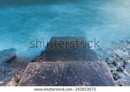 Stone steps leading towards the ocean in foreground  - stock photo