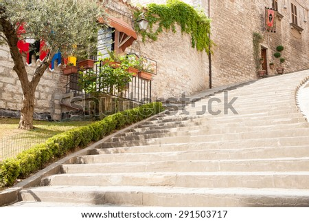 Stone steps leading up beside building and garden. - stock photo