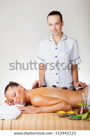 Stone-therapy. Beautiful young woman with closed eyes get a relaxing massage - stock photo