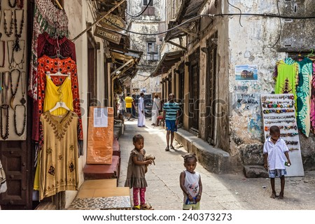 STONE TOWN, ZANZIBAR - OCTOBER 24, 2014: Local people on a typical narrow street in Stone Town. Stone Town is the old part of Zanzibar City, the capital of Zanzibar, Tanzania. - stock photo