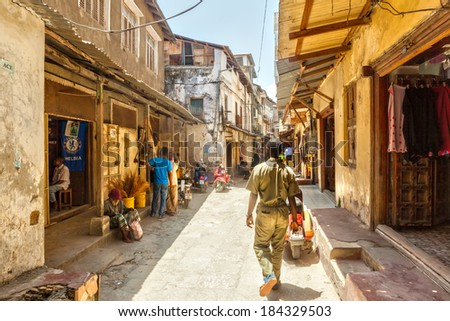 STONE TOWN, ZANZIBAR/TANZANIA - APRIL 4 2012: Local people on the streets in heart of city, which mostly consists of a maze of narrow alleys lined by houses, shops, bazaars and mosques.  - stock photo